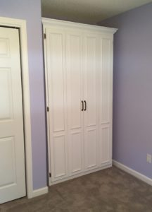 Twin painted MDF Murphy bed in tiny space.